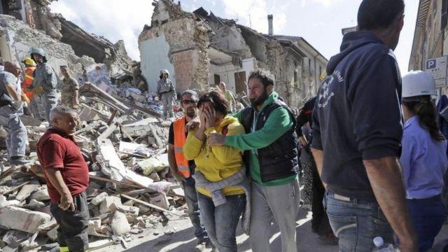 Una mujer llora, detrás el derrumbe que provocó el terremoto.
