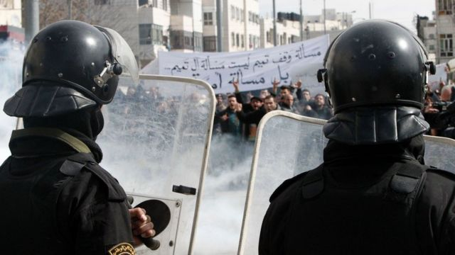 Palestinian policemen stand opposite demonstrators during a protest against a decision by the Palestinian Authority to grant public land to the Russian church, in the West Bank city of Hebron, on 4 February 2017