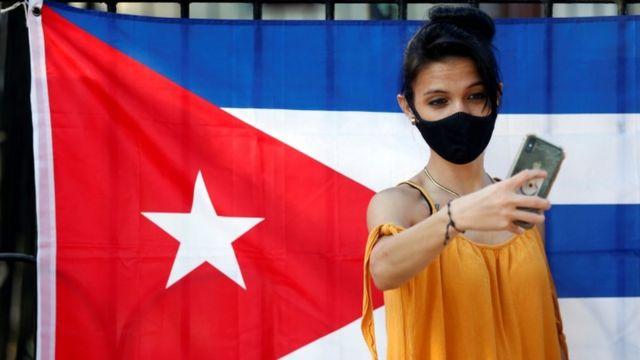 Cubana, frente a la bandera de Cuba.