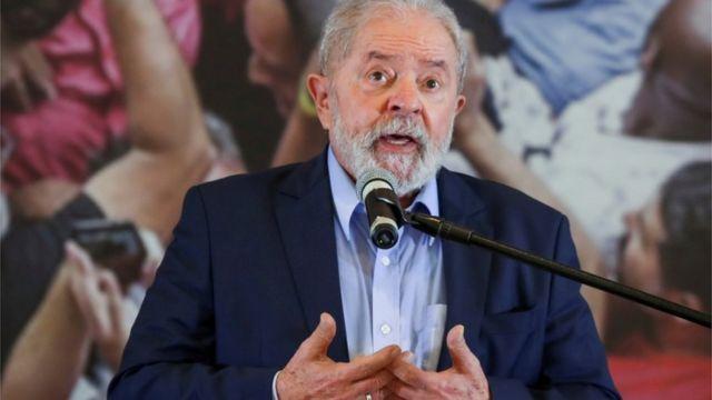 Lula fala ao microfone, em pé
