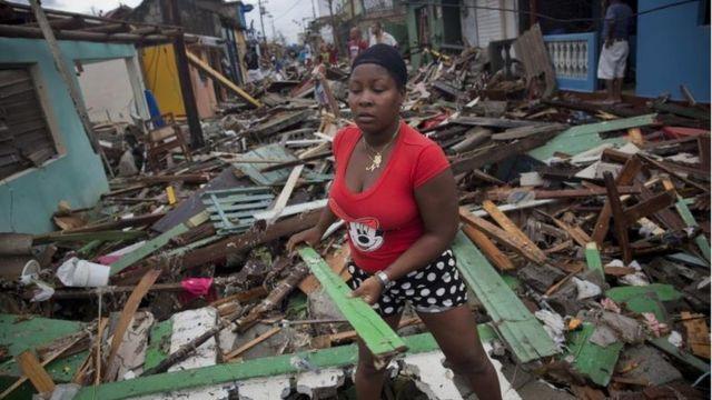 una mujer levanta escombros en Baracoa, Cuba