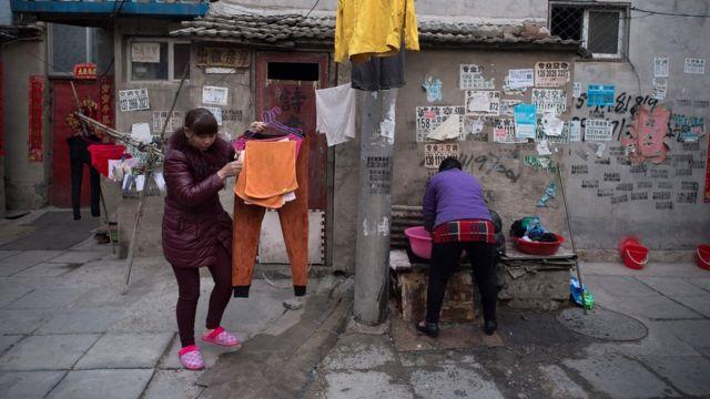북경의 이민자 마을에서 여성들이 옷을 세탁하고 말리고 있다