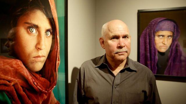 """El fotógrafo Steve McCurry posa con las imágenes enmarcadas de Sharbat Gula, conocida como la """"chica afgana"""""""