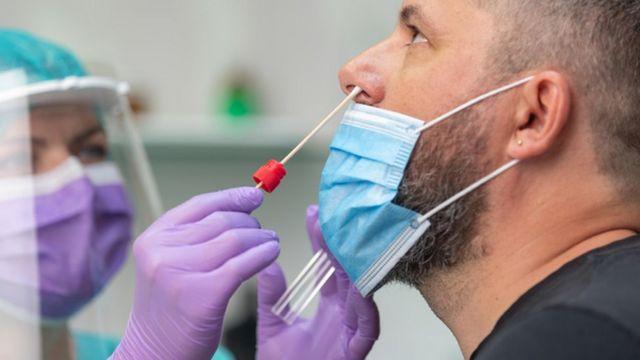 Un profesional de la salud coloca una uña flexible en la nariz del paciente para la prueba de covid-19