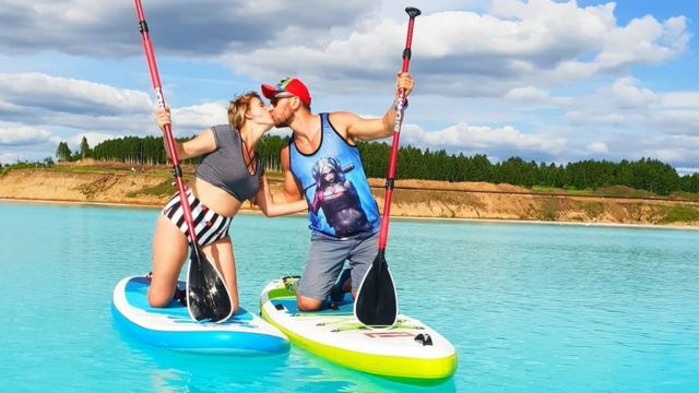 Una pareja besándose sobre tablas de paddle board en el lago Novosibirsk de Siberia