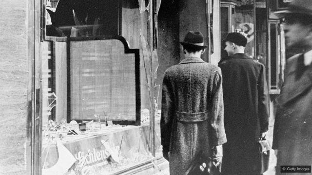 Des Allemands passent devant les vitres brisées d'un magasin au lendemain de la Nuit de Cristal, une nuit qui a montré au monde entier à quel point l'Allemagne devenait dangereuse pour les Juifs