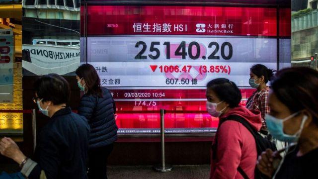 Unas personas caminan frente a una pantalla que muestra la caída de la bolsa de Hong Kong.