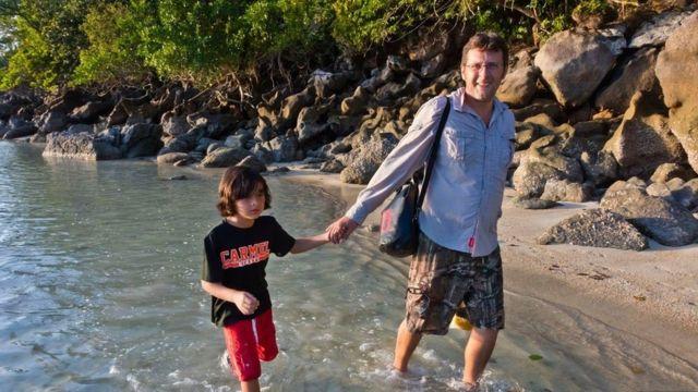 Un niño de la mano con su padre caminando en el agua.