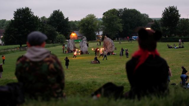 People celebrate the Summer Solstice in Avebury, despite official events being cancelled amid the spread of the coronavirus disease