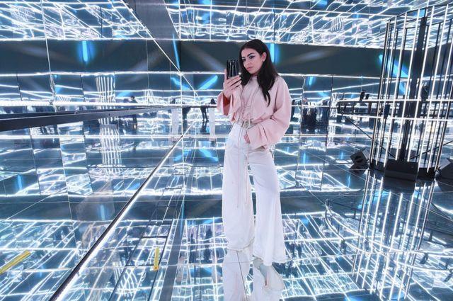 La cantante pop Charli XCX toma una fotografía en cubo de espejos
