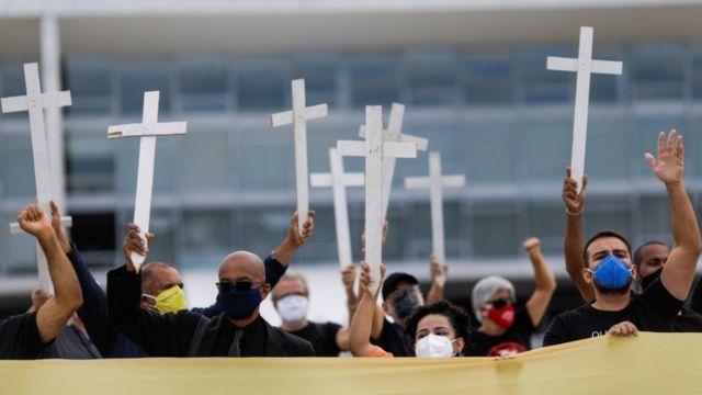 Pessoas com máscara levantando cruzes em protesto