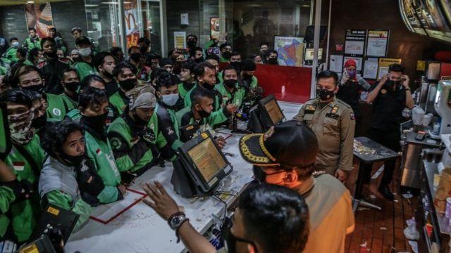 حشد من عُمال توصيل الطلبات إلى المنازل أمام إحدى فروع شركة ماكدونالدز للوجبات السريعة