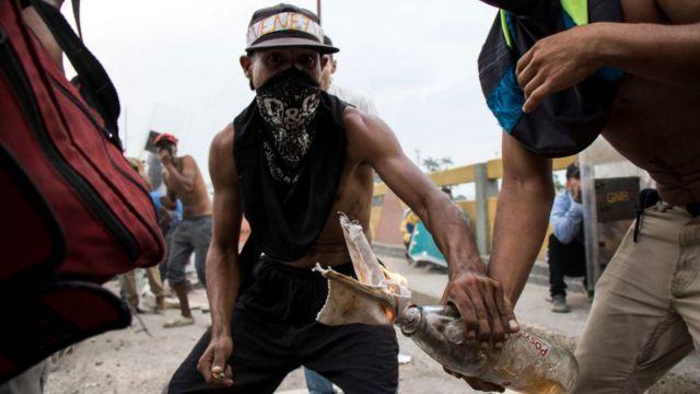 Homens encapuzados protestam durante tentativa de entrada de ajuda humanitária na Venezuela, no último fim de semana