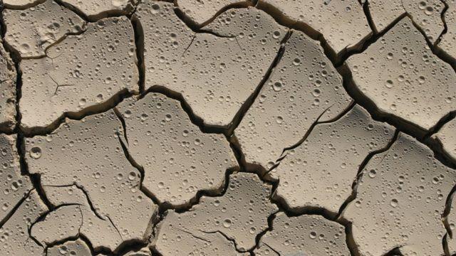 Suelo seco, cuarteado y rociado por gotas de agua.