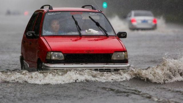 Un auto avanza por una calle inundada en Lianyungang, en la provincia de Jiangsu.