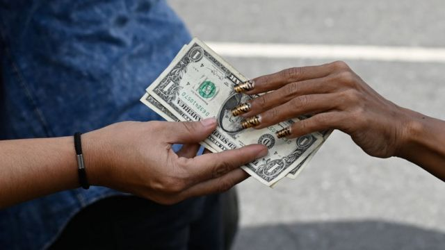 A woman's hand paying in dollars