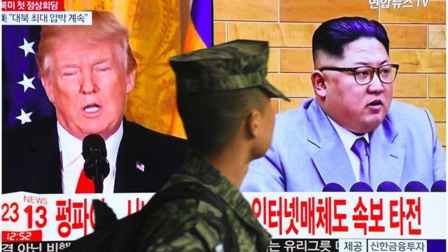 Un soldado surcoreano pasa junto a una pantalla con las imágenes de Trump y Kim Jong-un.