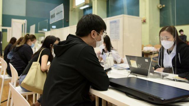 香港某社区疫苗接种中心内工作人员为已预约接种市民核对资料(中新社图片13/3/2021)