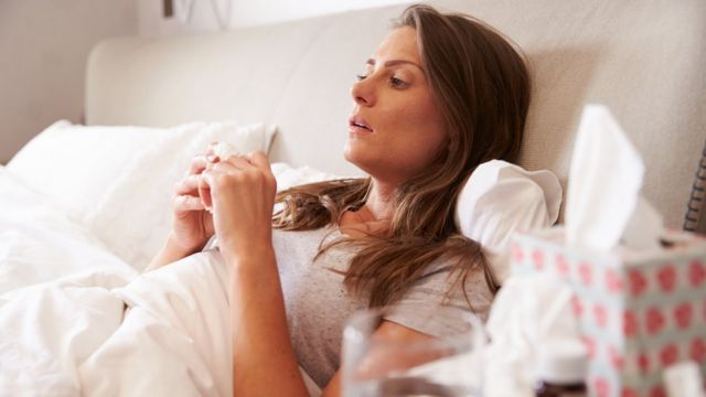 Mulher de cama com resfriado
