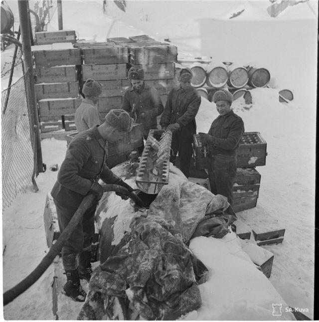 Soldados finlandeses enchem garrafas de coquetel molotov com combustível