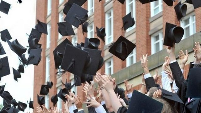 Graduates throw their mortar boards into the air