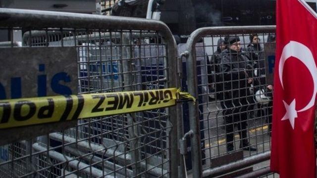 турецкий флаг на фоне полицейских заграждений