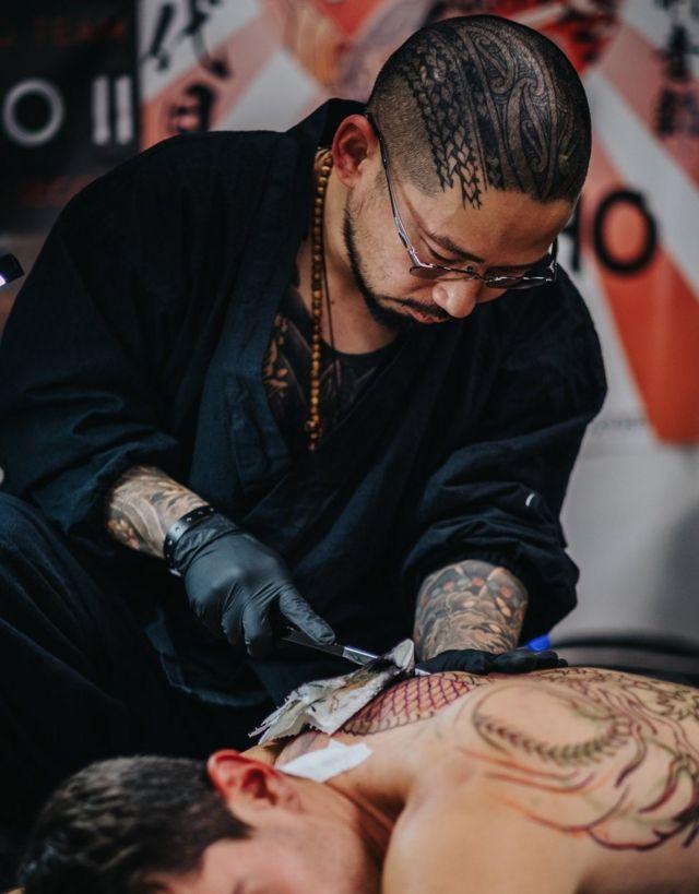 Kensho II works on a customer's tattoo