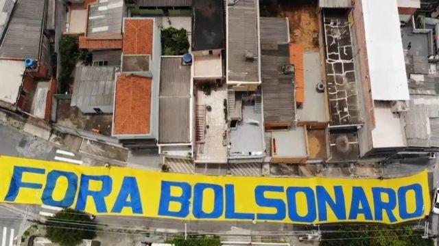 Faixa amarela colocada na rua e vista do alto diz 'fora bolsonaro' em azul; ao lado, telhados de casas