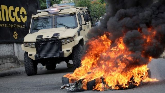 Security forces pass next to a fire set by demonstrators during a protest in Port-au-Prince, Haiti February 24,