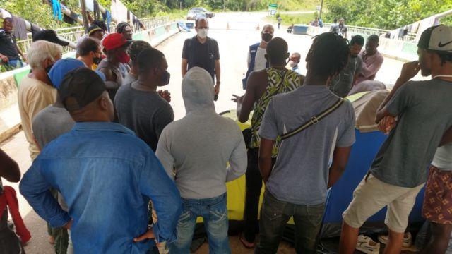 Em ponte, grupo de homens discute com agentes