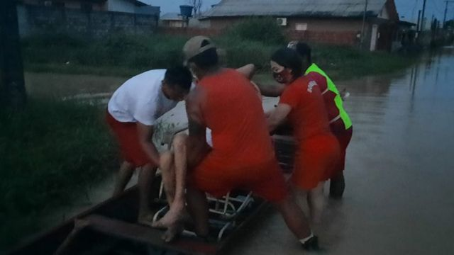 Bombeiros carregam idosa em barco durante alagamento