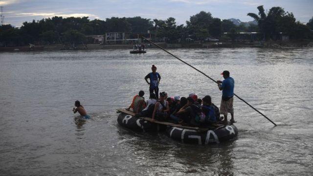Migrantes cruzan el río Suchiate en balsas