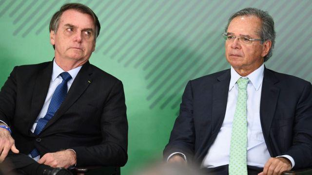 Jair Bolsonaro e seu ministro da Economia, Paulo Guedes, aparecem sentados durante evento