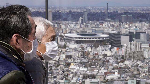 An elderly couple wearing protective face masks in front of the New National Stadium (background)