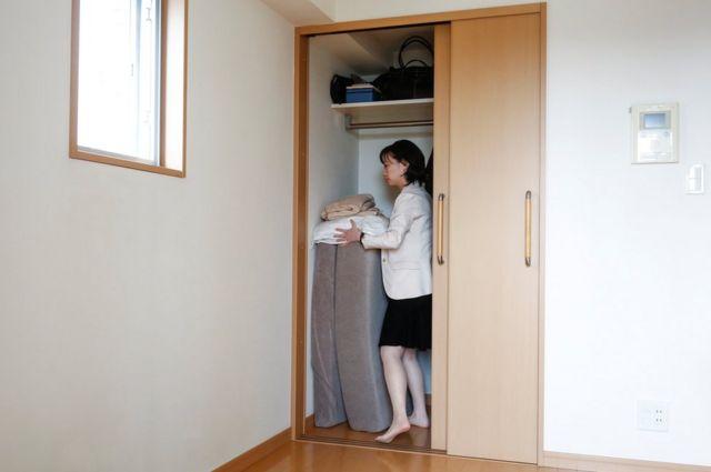 La minimalista Saeko Kushibiki guarda su futón en su apartamento en Fujisawa