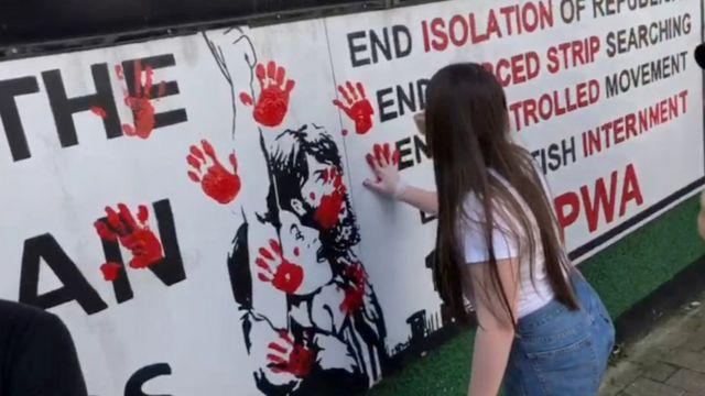 A woman smears a red hand print on a wall