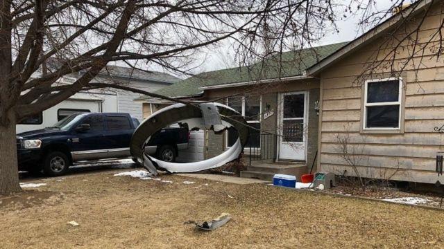 حطام لما يبدو إطار محرك طائرة أمام منزل