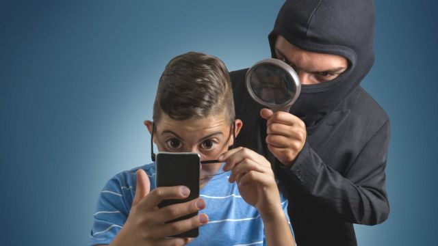 Niño mirando datos en un celular y un ladrón detrás.