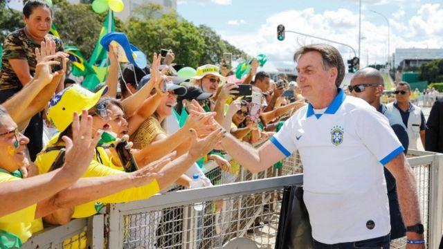 Bolsonaro aparece cumprimentando dezenas de seguidores do outro lado de cerca, vários deles com as mãos estendidas