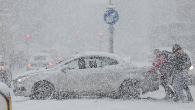 Car being pushed out of snow in Rochester, Kent, UK