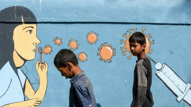 Boys walk past a painted graffiti to create awareness about coronavirus. Due to the spike of coronavirus cases in Maharashtra state, people have been advised to maintain social distance, wear masks and sanitize hands regularly.