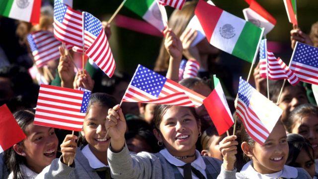 Niñas ondean banderas de México y EE.UU.