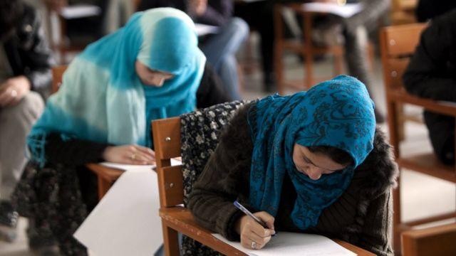 صورة امرأتين في معهد دراسي تكتبان