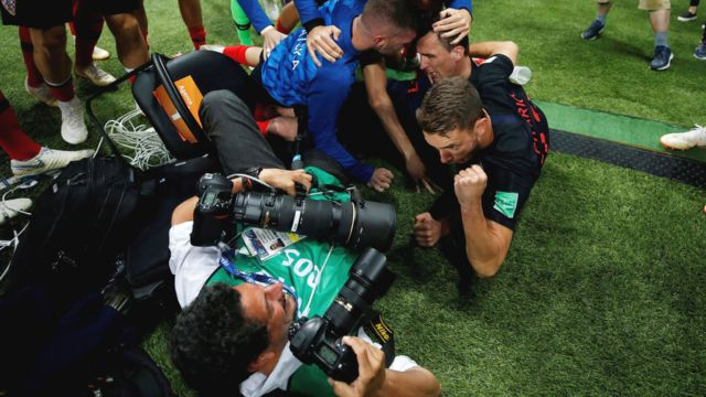 футболисты падают на фотографа