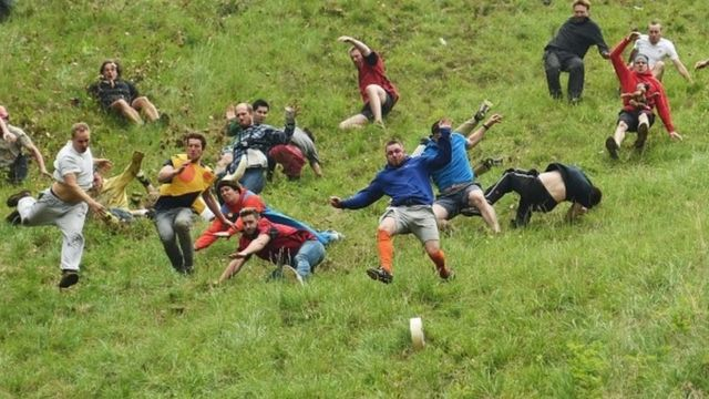 Competitors take part in the annual unofficial cheese rolling race at Cooper's Hill in Brockworth