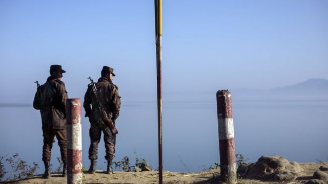 Border guards stand near the edge of the Naf river which separates Myanmar from Bangladesh is seen on February 6, 2017 in Teknaf, Bangladesh