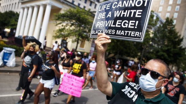 """Manifestante con un cartel que dice """"la vida no puede ser un privilegio blanco"""", en Washington D.C."""