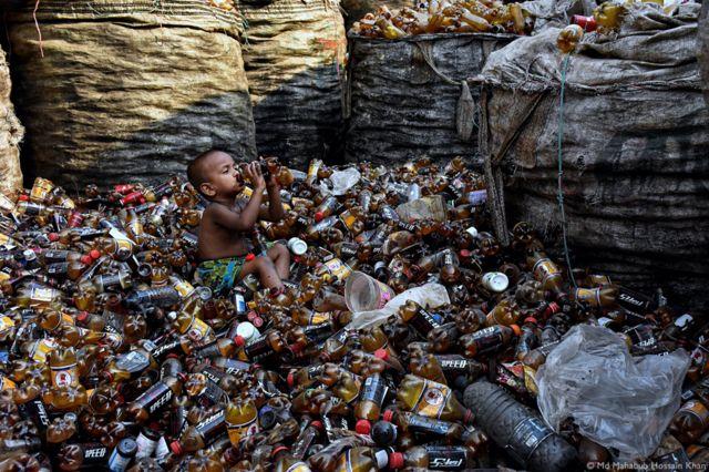 Un niño rodeado de botellas