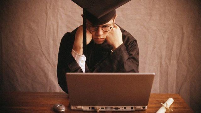 Jovem com beca e chapéu de formatura olha para um notebook com ar frustrado