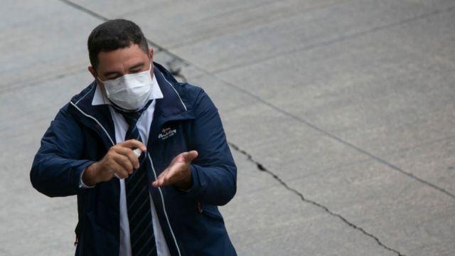 Un hombre con tapabocas rociándose gel antibacterial
